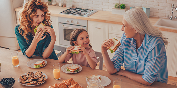 Three generations of women eating sandwiches