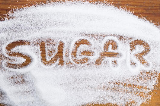 """sugar"" spelled in sugar on a table"
