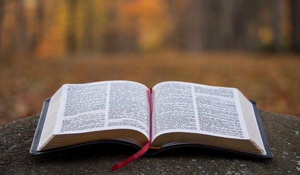 open bible in on concrete post