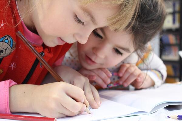 two girls writing in a workbook