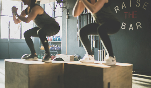 two women doing box jumps