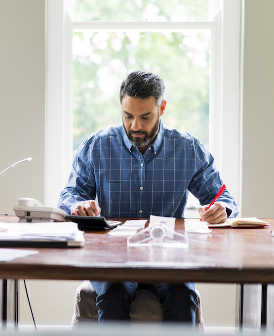 Man sitting at table crunching numbers