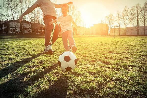 Kid playing soccer with dad