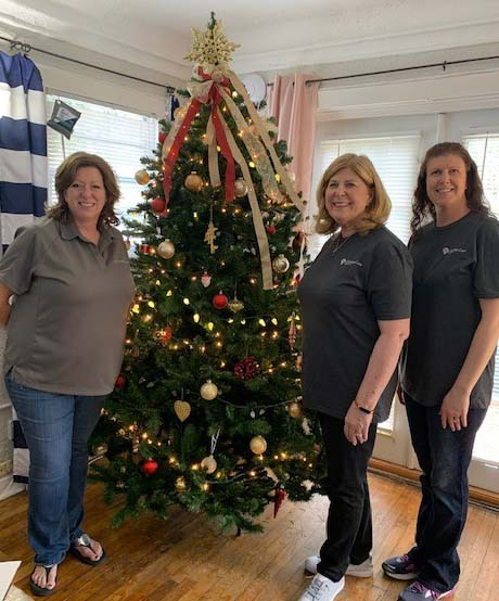 Ladies standing next to Christmas Tree