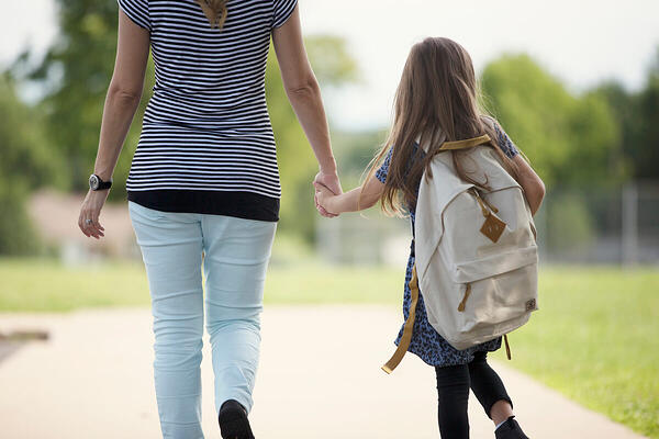 Mom walking daughter to school