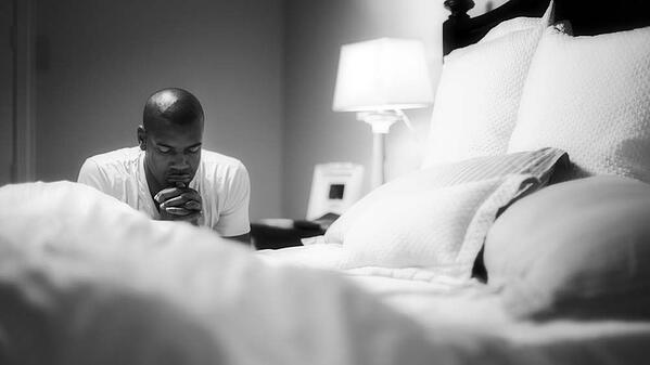 Man kneeling to pray by his bed