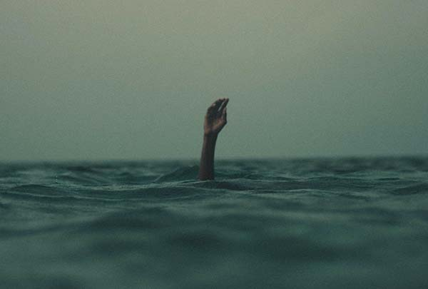 Hand reaching up from the water