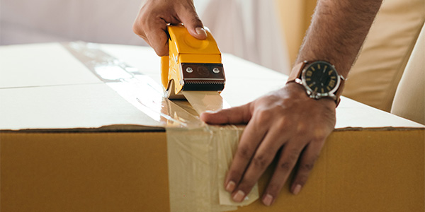 close up of hand taping up a box