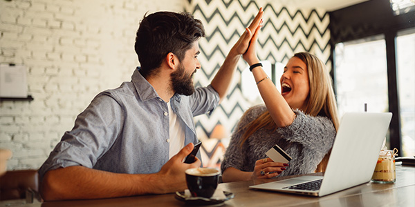 couple high fiving about finances