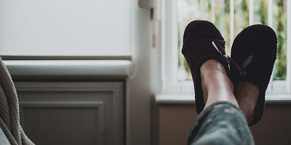 feet kicked up on couch with slippers