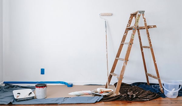 paint, dropcloth and ladder in a room