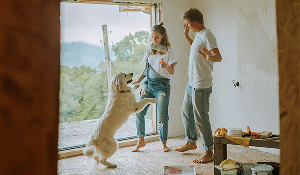 couple painting while playing with dog