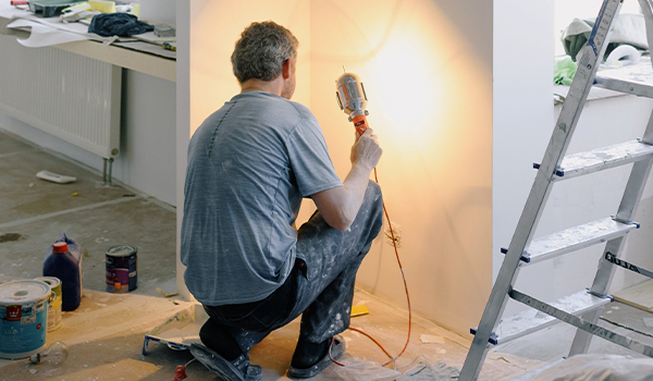 man in unfinished home shining light on wall