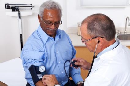 doctor taking blood pressure of man