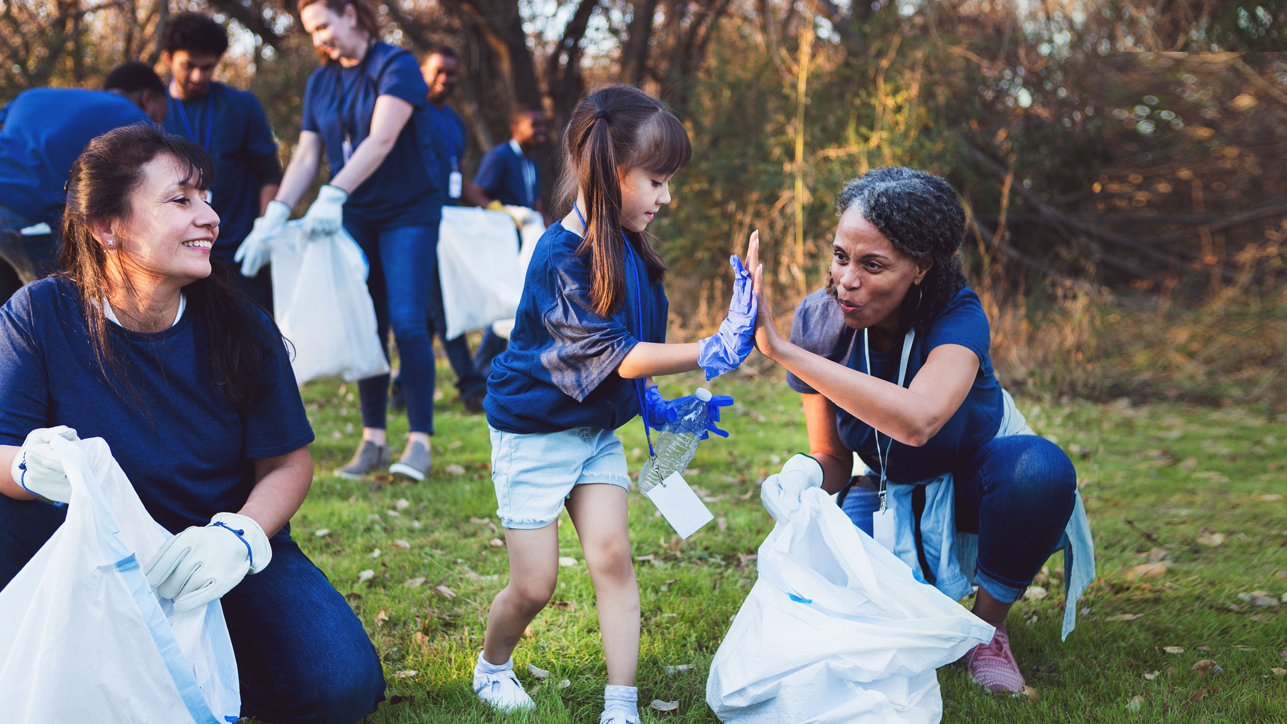 A child giving an adult a high five while volunteering