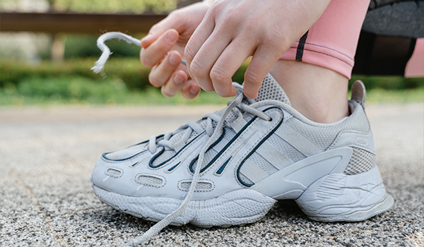 lacing up tennis shoes