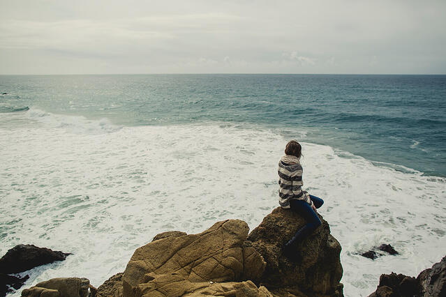 A woman sitting on the edge of a boulder overlooking the ocean.