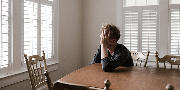 man sitting at kitchen table with head in hands looking frustrated