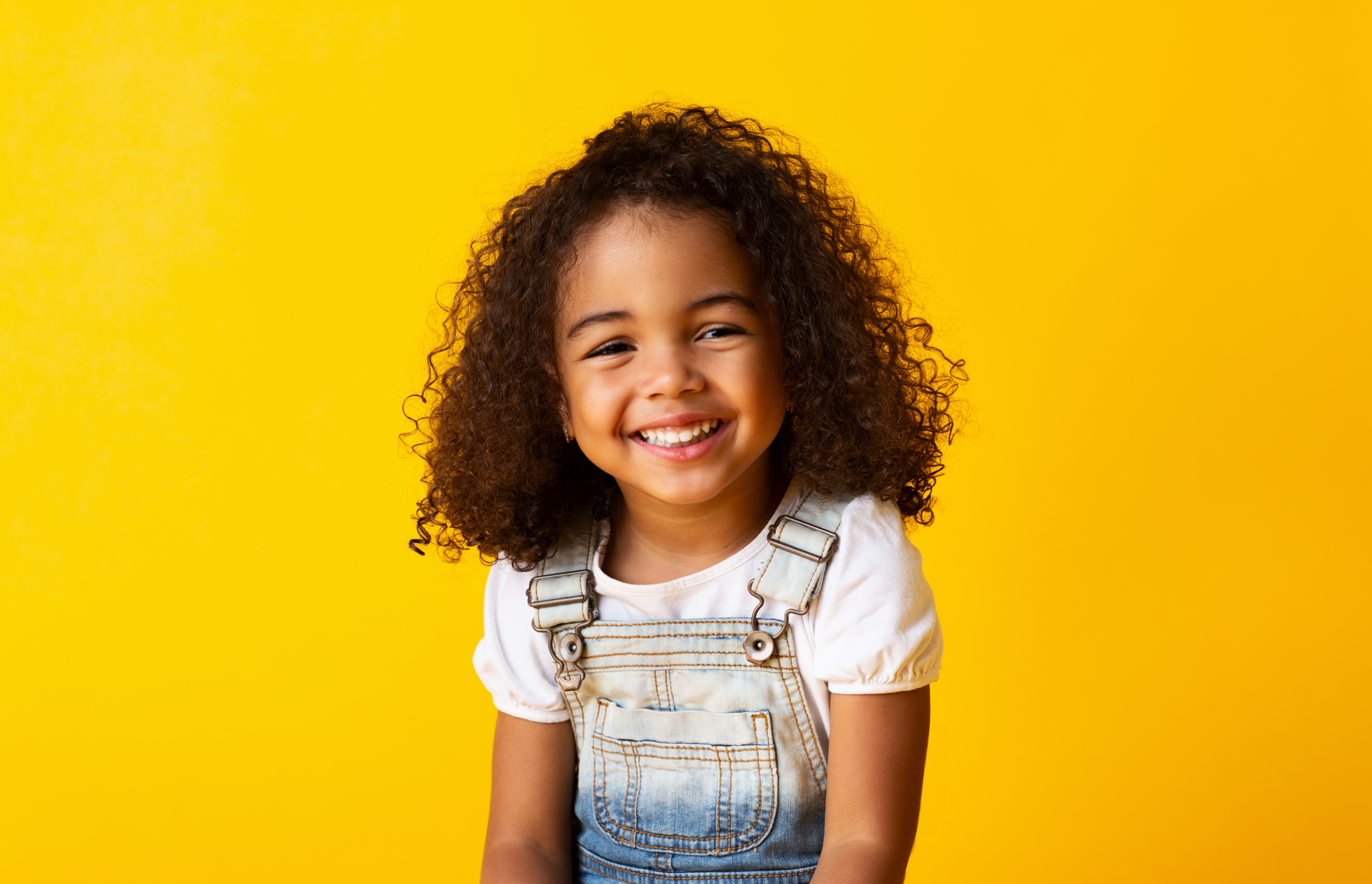 A young girl smiling for a picture.