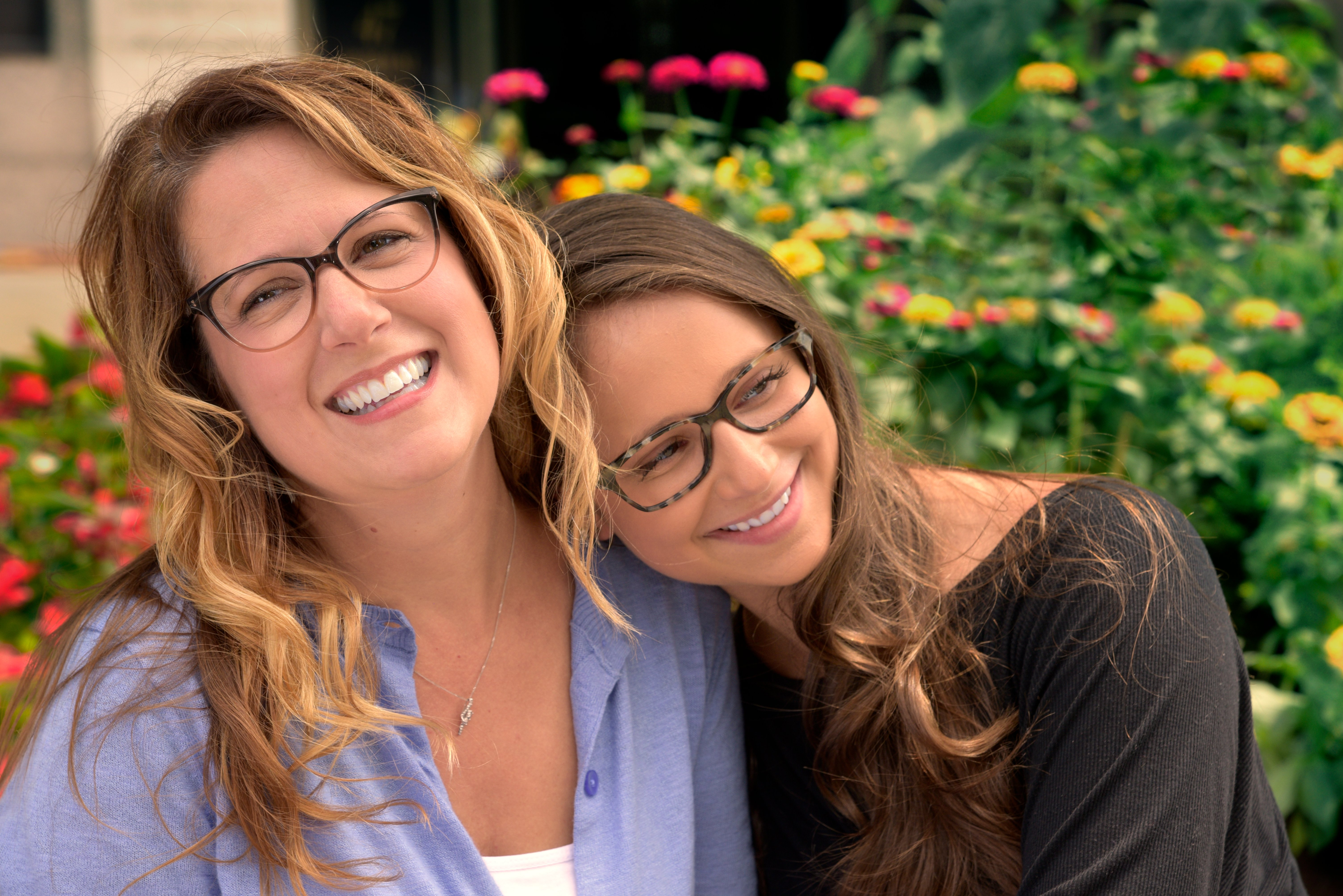 A mother and Daughter posing for a picture while wearing Eyes of Faith glasses.